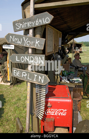 World War II replica signs to New York, London, Berlin and Shirley with mileage totals in front of tents - Stock Photo
