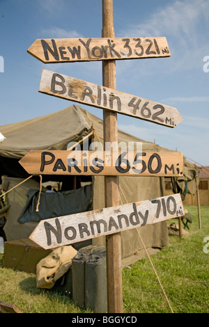 World War II replica signs to New York, London, Berlin and Normandy with mileage totals in front of tents at Mid - Stock Photo