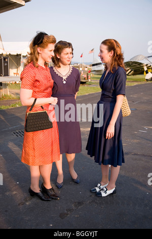 Three women wearing old fashioned 1940s dresses at Mid-Atlantic Air Museum World War II Weekend and Reenactment - Stock Photo
