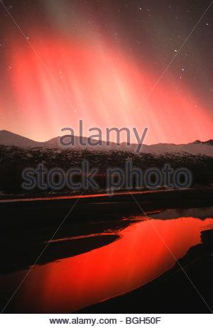 Alaska, Aurora Borealis northern lights, Hues of Red and Yellow above Knik River and Chugach Mountains. - Stock Photo