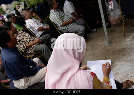 A muslim female reporter using short hand to make notes in Malaysia - Stockfoto