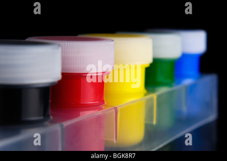 Tubes of colorful acrylic paint isolated on black background - Stock Photo