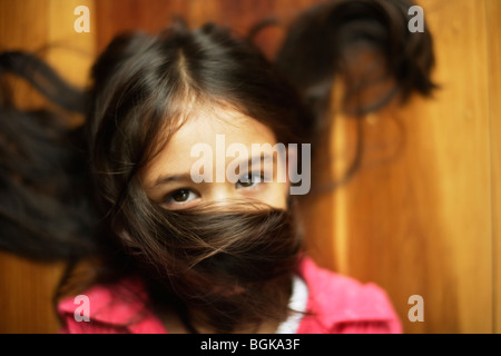 Girl six years old with hair across face - Stock Photo