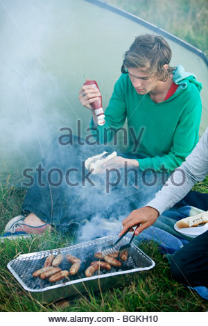 Two young men cooking sausages on a barbecue - Stock Photo