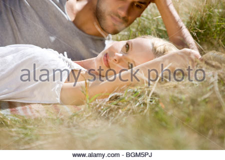 A young romantic couple relaxing on the grass - Stock Photo