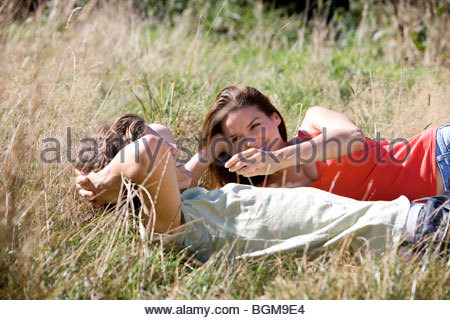 A young couple lying on the grass - Stock Photo