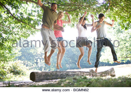 Four friends jumping from a log - Stock Photo