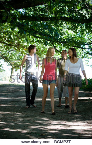 Four friends walking along a path - Stock Photo