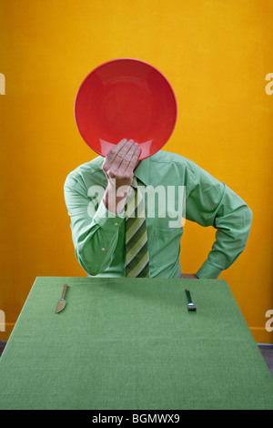 man holds red dinner plate over face while sitting at green table. - Stock Photo