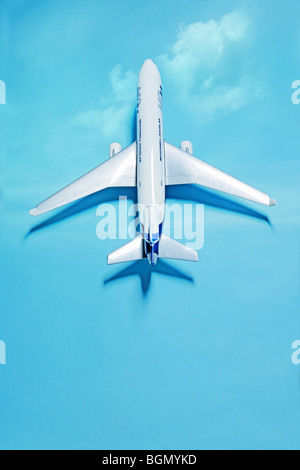 white model airplane on blue with shadow - Stock Photo