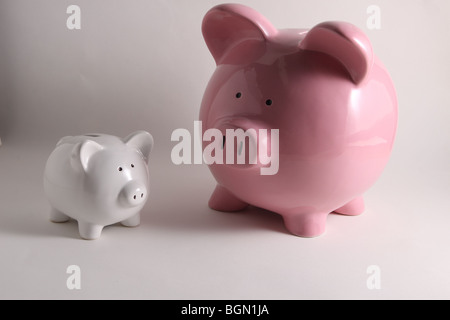 two piggy banks. One large pink piggy bank and one small white piggy bank - Stockfoto