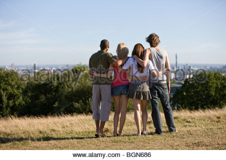 Four friends in a park looking across the city, rear view - Stock Photo
