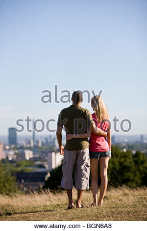 A young couple in a park, looking across the city - Stock Photo