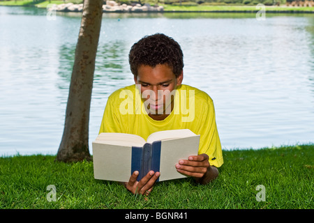 16-17 year old teenage Hispanic/African American boy young man  relaxing relaxes reading in park under tree shade - Stock Photo