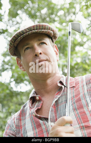 Close-up of a mature man holding a golf club - Stock Photo