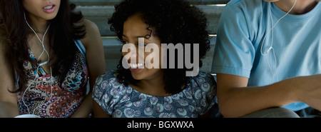 Junge Frau sitzt zwischen zwei Freunden Kopfhörer anhören, wegschauen und lächelnd - Stockfoto