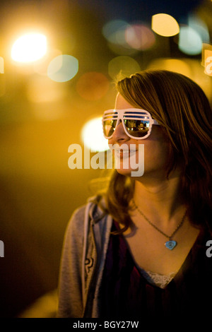 A 13 year old girl wearing sunglasses at night in Hollywood, CA - Stockfoto