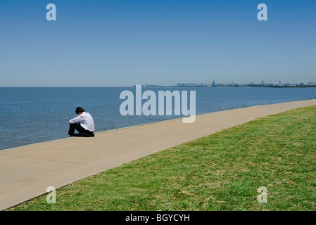 Man in business attire sitting by sea with head down - Stock Photo