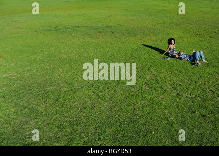 Young couple relaxing together in park, high angle view - Stock Photo
