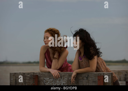 Two young women outdoors, leaning on railing, looking away - Stock Photo