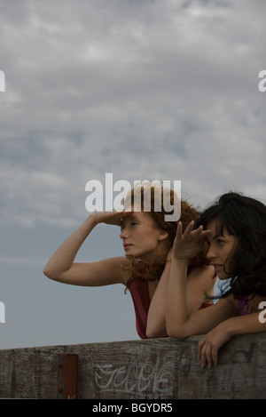 Two young women outdoors looking at view - Stock Photo