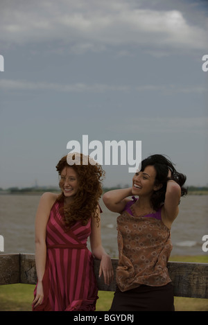 Two young women standing outdoors, laughing - Stock Photo