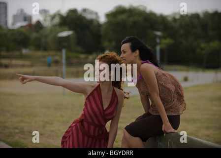 Two young women outside in park together, one pointing out of frame - Stock Photo