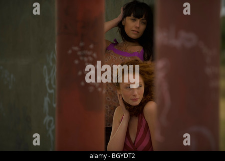 Two young women, wind in hair, both brushing hair back - Stock Photo