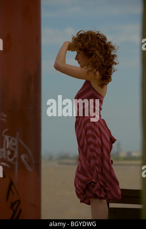 Young woman standing near coast, looking to distance - Stock Photo