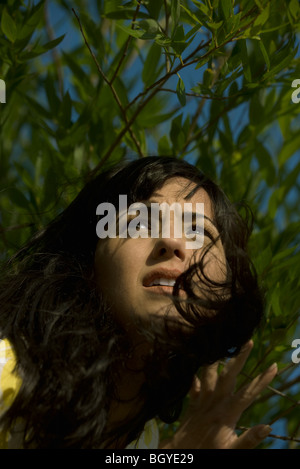 Young woman coming through foliage, looking away and furrowing brow - Stock Photo