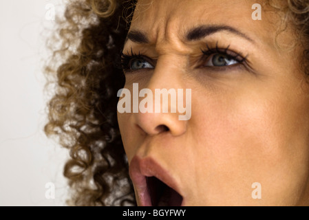 Woman furrowing brow, shouting , close-up - Stock Photo