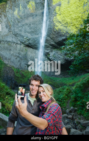 Couple taking picture in front of waterfall - Stock Photo