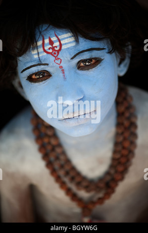 Indian boy, face painted as the Hindu god Shiva against a black background. India - Stock Photo