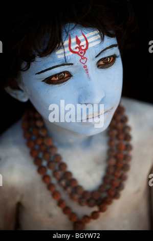 Indian boy, face painted as the Hindu god Shiva against a black background - Stockfoto