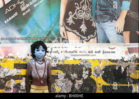 Indian boy, face painted as the Hindu god Shiva standing in front of a Bollywood movie poster - Stock Photo