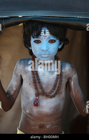 Indian boy, face painted as the Hindu god Shiva standing in a rickshaw - Stock Photo