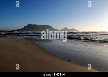 Table Mountain silhouetted during a glorious and dramatic sunset viewed from Milnerton beach Cape Town capetown - Stock Photo