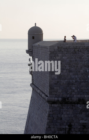 couple taking photograph City wall of Dubrovnik old Town Croatia dusk - Stock Photo