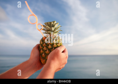 A man's hands holding a tropical pineapple cocktail drink with a straw against a blue sea and sky - Stock Photo