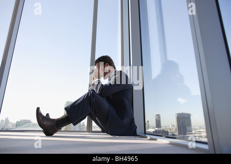 A businessman sitting on the floor in the corner of an office skyscraper with his head in his hands - Stock Photo