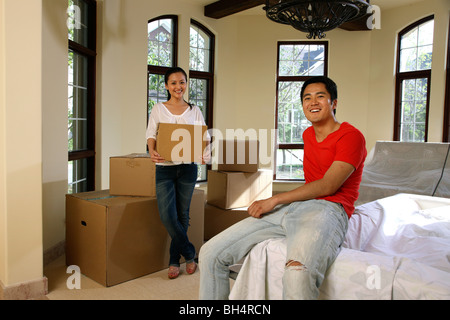 Couple moving house carrying stack of cardboard boxes side by side stock photo royalty free - Young couple modern homes ...
