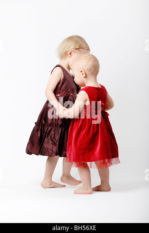 Two little girls dancing on white background - Stockfoto