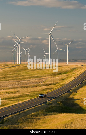 A pick-up truck on a lonely road is dwarfed by wind turbines at the Judith Gap wind farm - Stockfoto