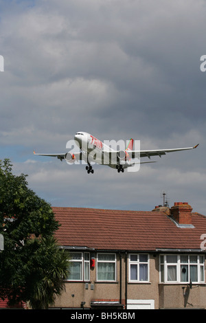 TAM Airlines Airbus A330 overflying London rooftops en route to Heathrow - Stock Photo