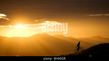 Mountain biker rides up a hill at sunset. This one is in Arizona, just west of Tucson. - Stock Photo