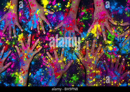Multicoloured powder hands on black. India - Stock Photo