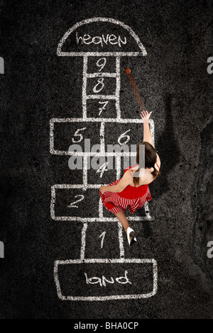 Beautiful young woman playing hopscotch with a red dress - Stock Photo