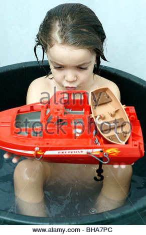 CHILD CHILDREN KID BOY KIDS playing with a red toy boat in a tub of water BATHROOM BATH BATHING Toddler infant toddlers - Stock Photo