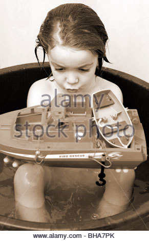 CHILD CHILDREN KID BOY KIDS in the bath with a toy boat - Stock Photo