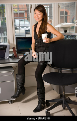 http://n450v.alamy.com/450v/bhabfh/young-asian-woman-in-office-sitting-on-desk-with-coffee-looking-at-bhabfh.jpg